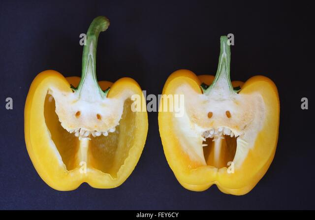 Close-Up Of Halved Yellow Pepper With Anthropomorphic Face - Stock Image