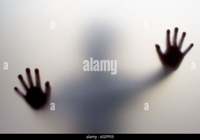 The hands of a child pressed up against the frosted glass of a door - Stock-Bilder