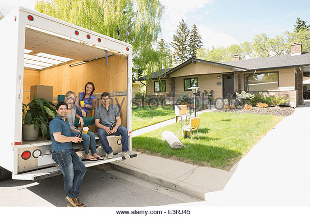 Portrait of couples at back of moving van - Stock Image