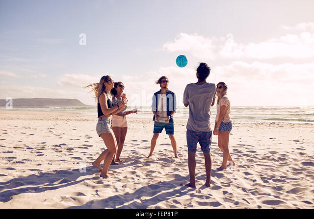 Group of young people playing with ball at the beach. Young friends enjoying summer holidays on a sandy beach. - Stock-Bilder