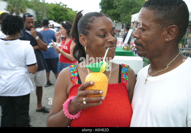 Florida Coconut Grove Grand Avenue Bahamas Goombay Festival Black couple man woman tropical drink - Stock Image
