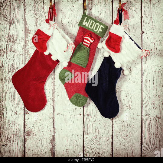 Christmas stocking hanging against rustic wood background - Stock Image