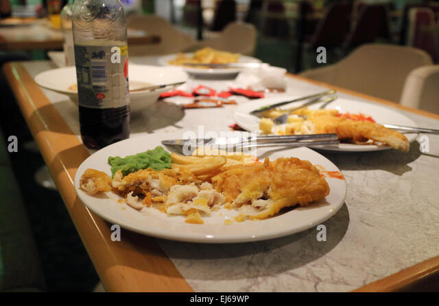 half eaten fish and chips meals in a cafe restaurant in the uk - Stock Image