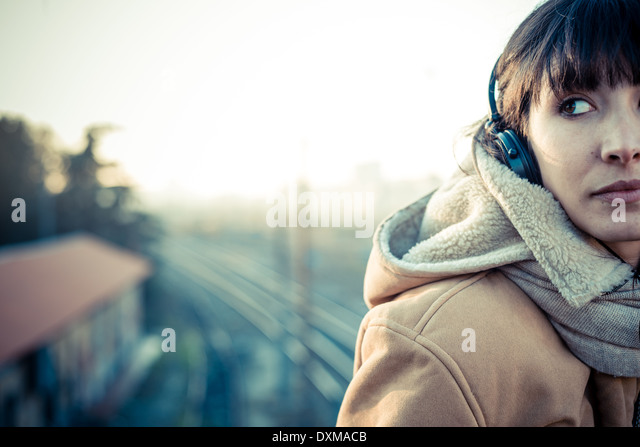 beautiful young woman listening to music headphones in the city winter - Stock Image