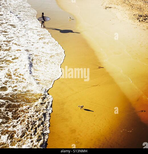A male Surfer walks up the beach after surfing. Manhattan Beach, California USA. - Stock-Bilder