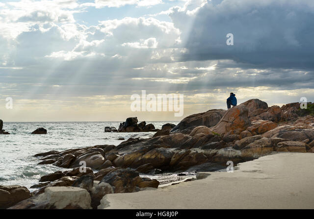 A man sits on rocks on a beach looking at the ocean with gods rays sunlight shining through clouds - Stock Image