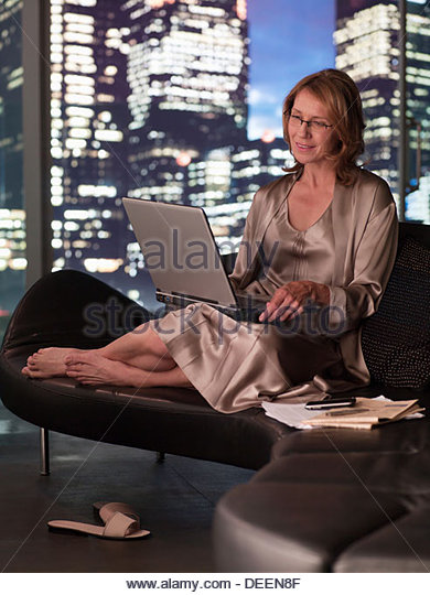 Woman in nightgown using laptop at night - Stock-Bilder