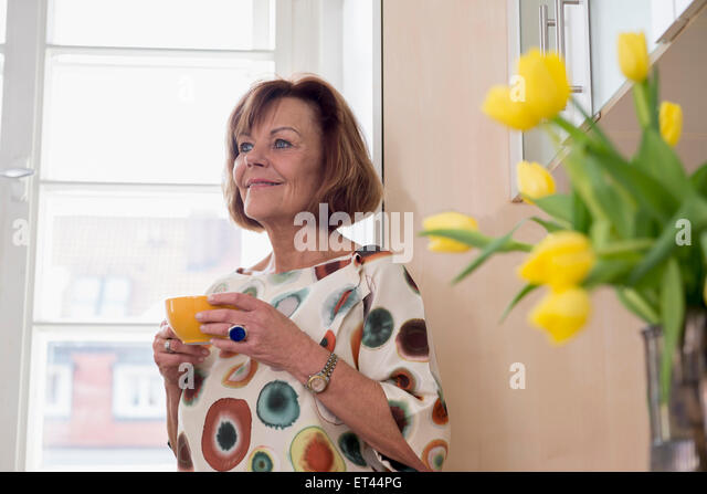 Senior woman dreaming while drinking tea in kitchen Munich, Bavaria, Germany - Stock-Bilder