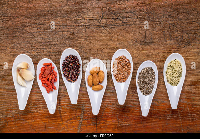 superfood grain, seed, berry, nuts and garlic cloves abstract - top view of spoon bowls against rustic wood with - Stock Image