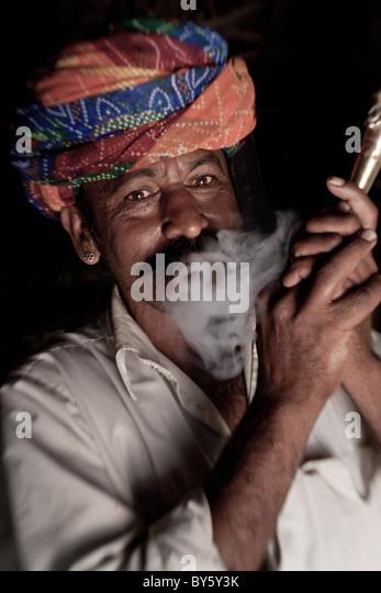 Indian man (member of Bishnoi religous sect) smoking a pipe, nr Jodhpur, Rajasthan, India - Stock-Bilder