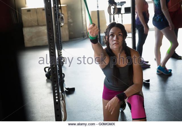 Focused woman using resistance band at gym - Stock-Bilder