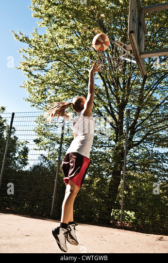 Teenage girl playing basketball - Stock Image