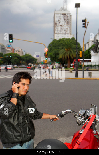 Buenos Aires Argentina Avenida 9 de Julio street scene Hispanic man young adult motorcycle leather jacket talking - Stock Image