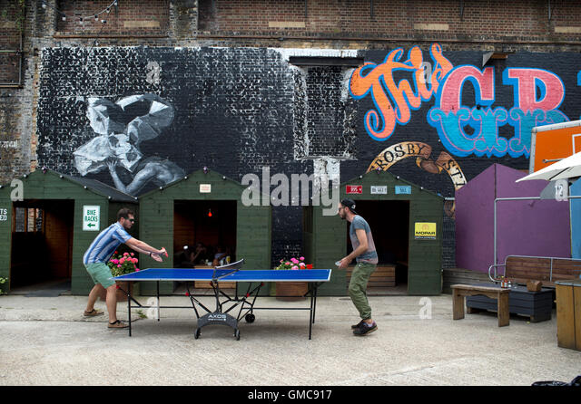 Hackney Wick. Two young men play table tennis. - Stock Image