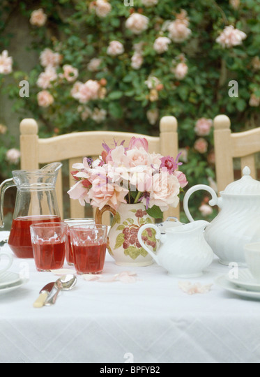 Close-up of pink roses on table set for tea in the garden with white teapot and glasses of fruit-juice - Stock Image