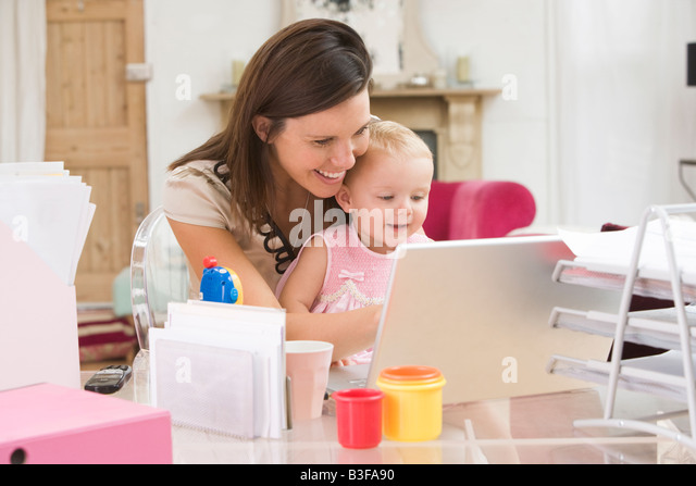 Mother and baby in home office with laptop - Stock Image
