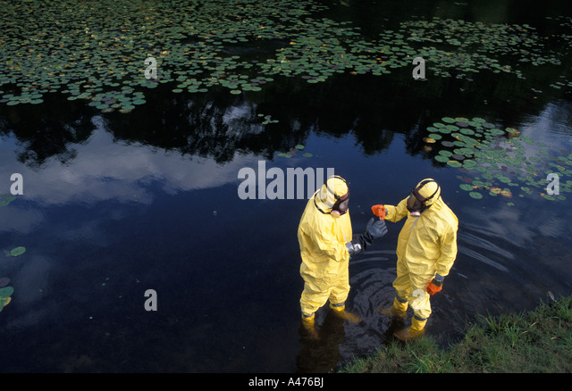 Two workers in protective suits test chemical levels in a body of water - Stock Image
