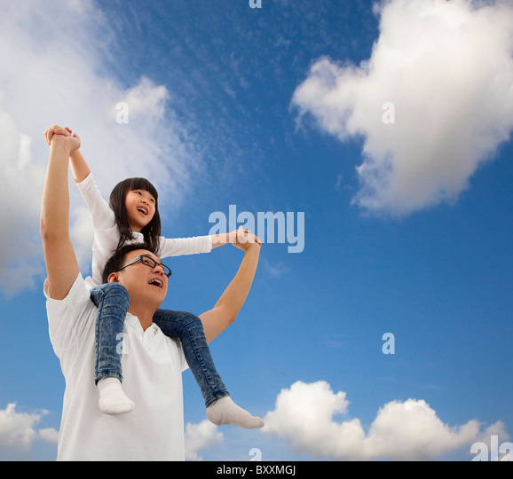 Asian father and daughter under cloudfield - Stock Image
