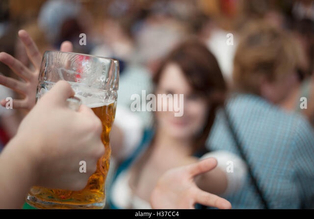 Excited girl reaches for a mug of beer at Oktoberfest - Stock Image