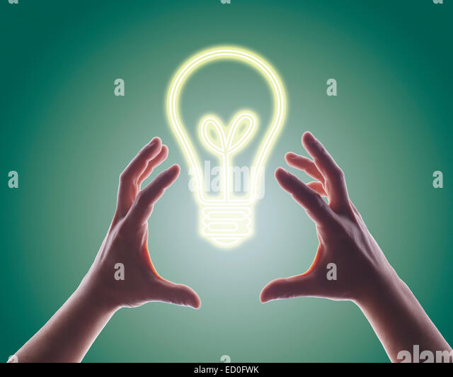 Person's hands reaching for digitally generated image of light bulb - Stock Image