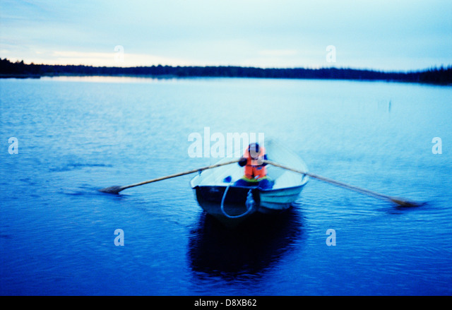A Child Rowing a Boat. - Stock Image