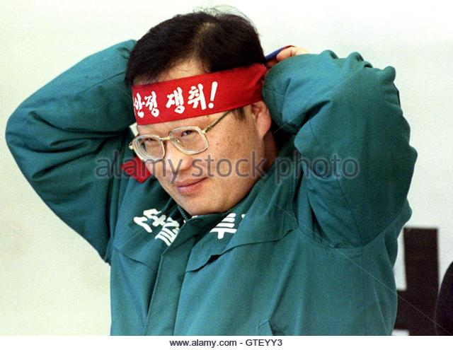 A South Korean labour leader puts on a headband reading 'Let's fight to get employment stability,' prior - Stock Image