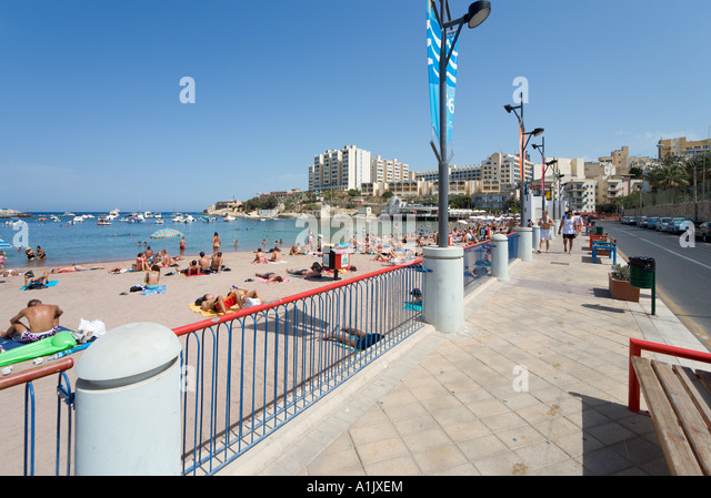 Beach and seafront promenade at St George's Bay, Malta - Stock Image