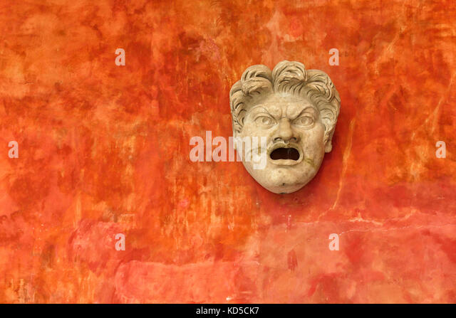 Stone face of angry man against a bright orange wall. Ancient Roman head in museum Glyptotek in Copenhagen, Denmark - Stock Image