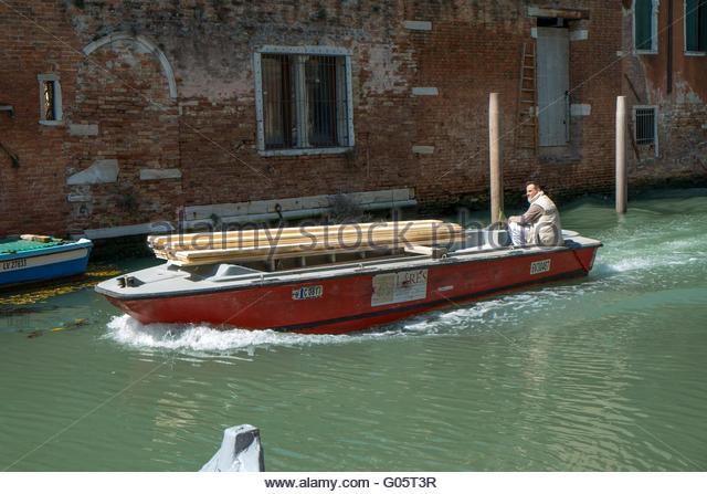 Boat transporting timber Venice, Italy, April - Stock-Bilder