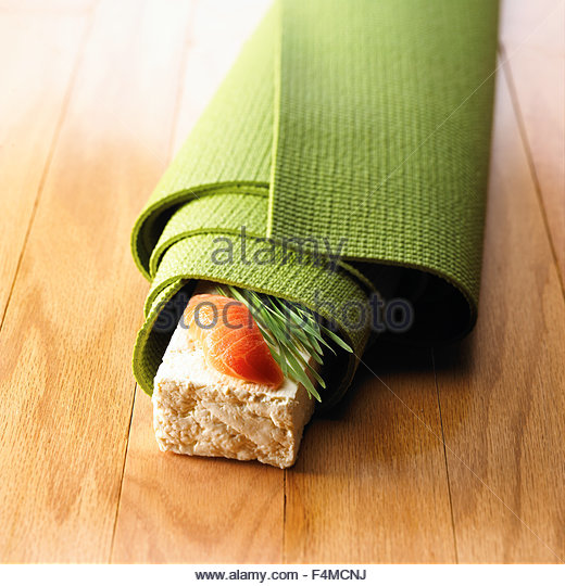 Sashimi Salmon on tofu slice with herbs wrapped with yoga mat - Stock Image