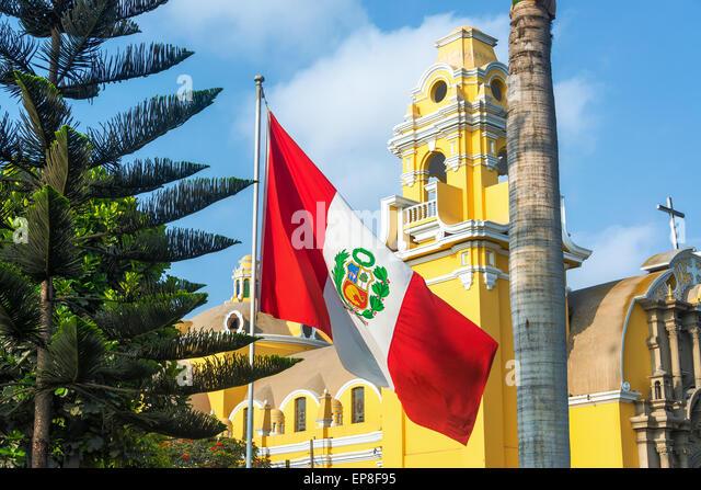 Peruvian flag and yellow church in the Barranco neighborhood in Lima, Peru - Stock Image