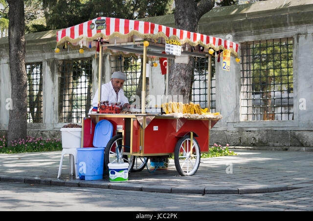 Istanbul, Turkey - April 16, 2017: Old man selling chestnut and corn on traditional Turkish fast food cart in Sultan - Stock Image
