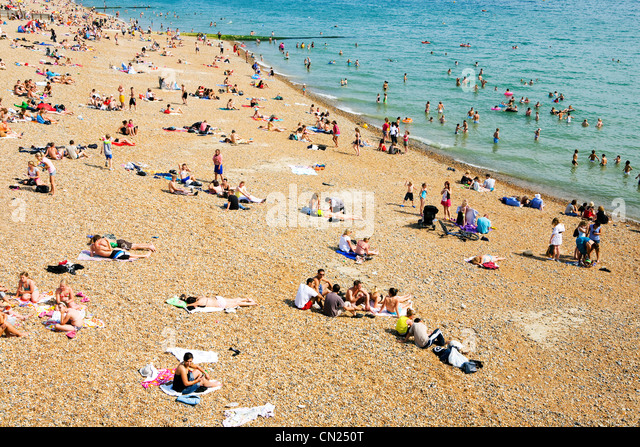 People on crowded beach, Brighton, England - Stock Image
