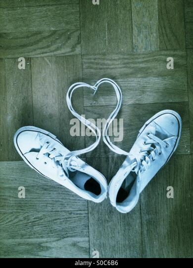 Heart shape in laces with white trainers on a wooden floor. - Stock Image