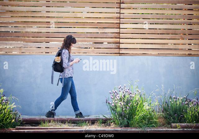 A woman walking down urban neighborhood sidewalk with a cat in her backpack. - Stock-Bilder