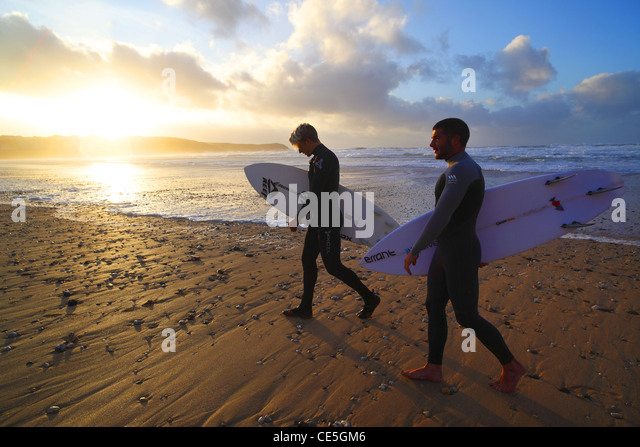 Surfers watch the winter sun go down on Fistral Beach in Newquay, Cornwall, UK. - Stock Image