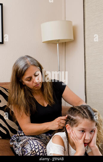 Mother and daughter Family lifestyle parenting showing a tired Mum styling her young daughter's hair into plaits - Stock Image