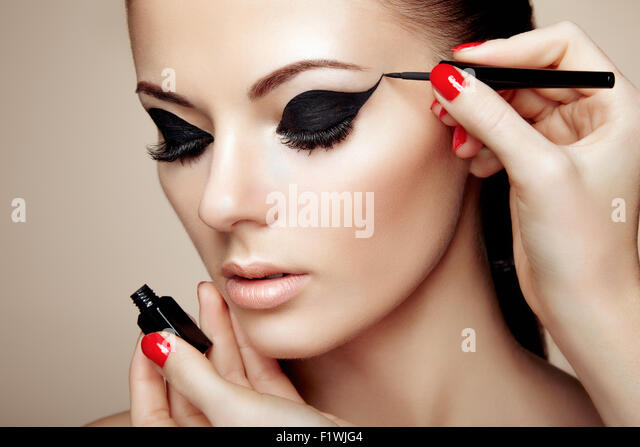 Makeup artist applies eye shadow. Beautiful woman face. Perfect makeup - Stock Image