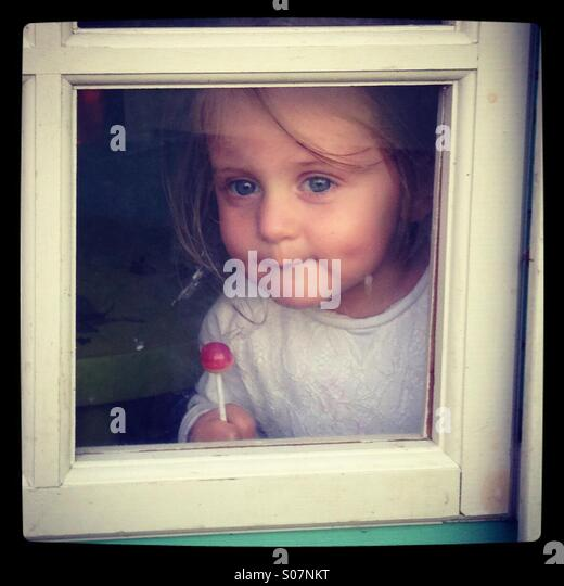 Girl in a window - Stock Image