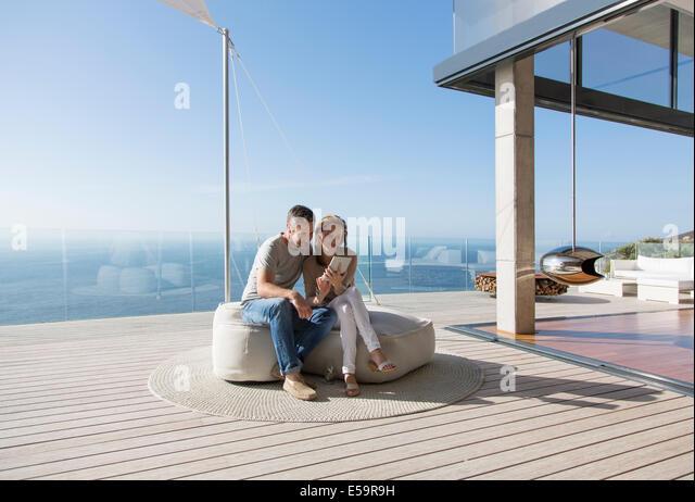 Couple using digital tablet on modern balcony - Stock Image