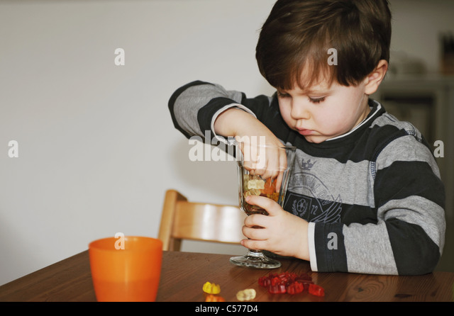 Boy playing with candy at table - Stock Image