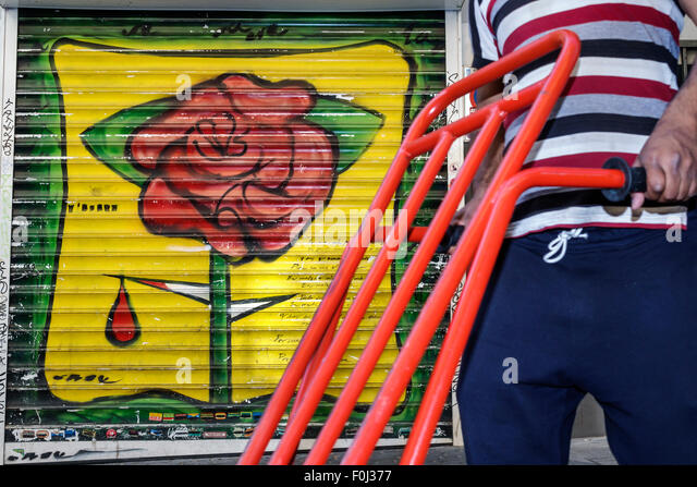 Spain Europe Spanish Madrid Centro Lavapias Calle de Zurita mural rose thorn blood pedestrian - Stock Image