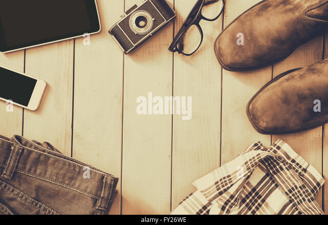 top view image of hipster accessories and clothes a wooden background. sepia vintage filtered - Stock Image