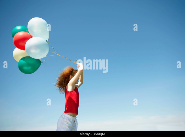 Young girl holding bunch of balloons - Stock Image