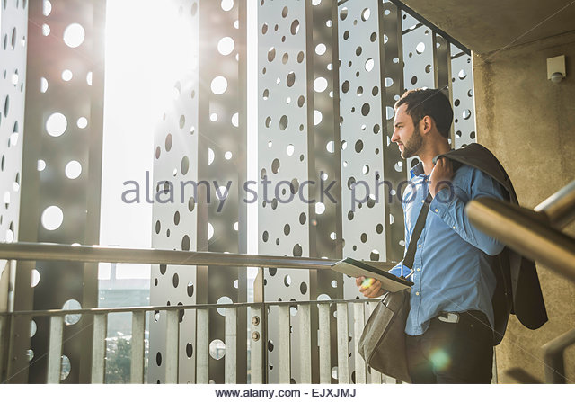 Young businessman with digital tablet looking out of window - Stock Image