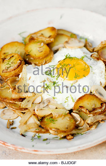 Fried potatoes with fried egg, fennel and mushrooms - Stock Image