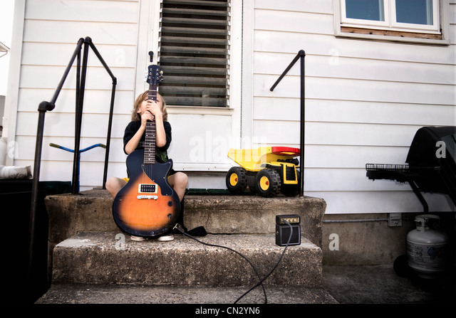 Shy boy and his guitar - Stock Image