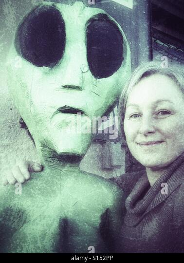 A woman with an alien buddy. - Stock Image