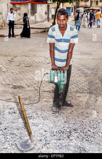 India Asian Mumbai Dharavi Shahu Nagar Road slum man electric jackhammer roadwork road repair working job - Stock Image