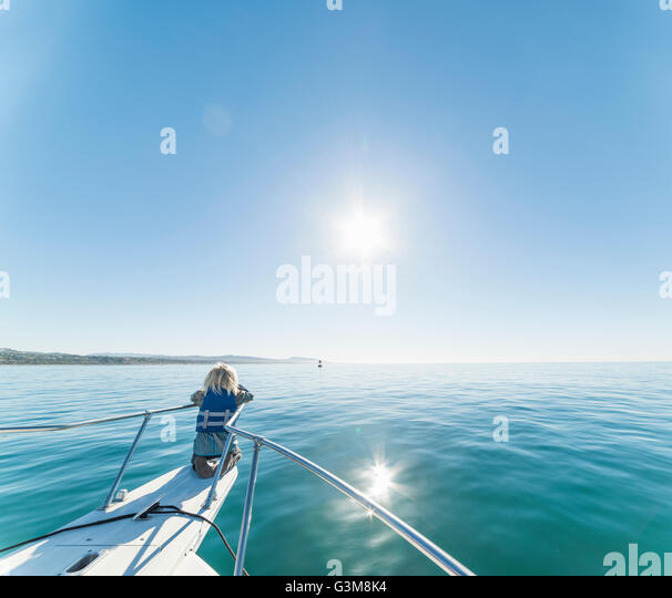 Boy kneeling on ships bow of sailboat looking away - Stock Image